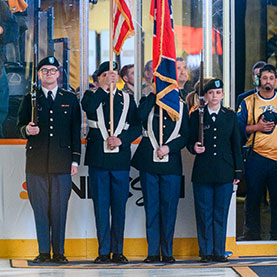 Photo of military people holding flags at a hockey game. Links to Tangible Personal Property