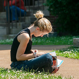 Photo of a student sitting in the grass. Links to Gifts of Appreciated Securities